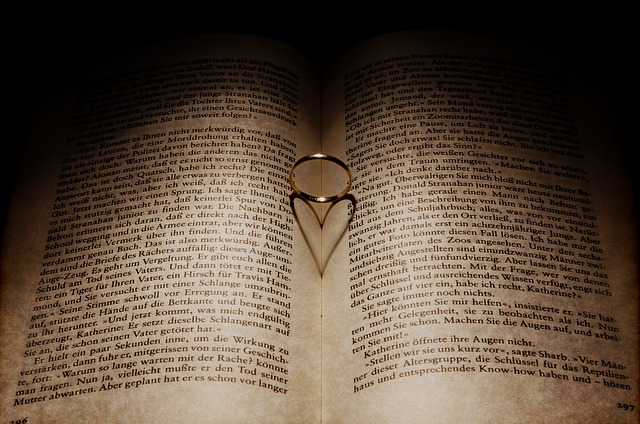 An open book with a god ring in the centre causing a heart shadow