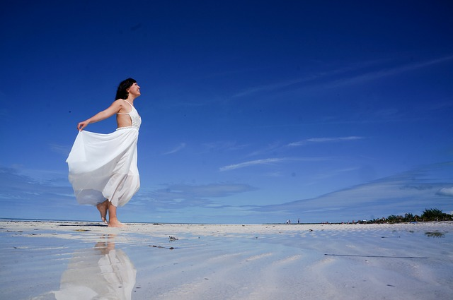 Lady in a white dress standing on the beach