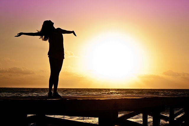 Girl standing on a jetty at sunset