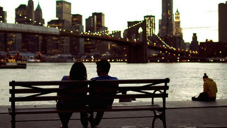 Couple sitting by a bridge in the city