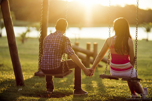 A couple sitting on swings holding hands