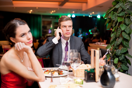 Man on his mobile phone during a date