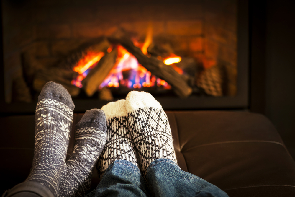 A couple's feet in front of the fire
