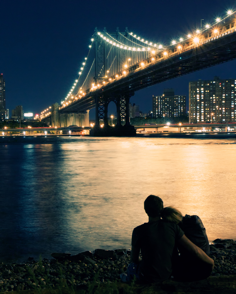 A couple sitting by bridge at night