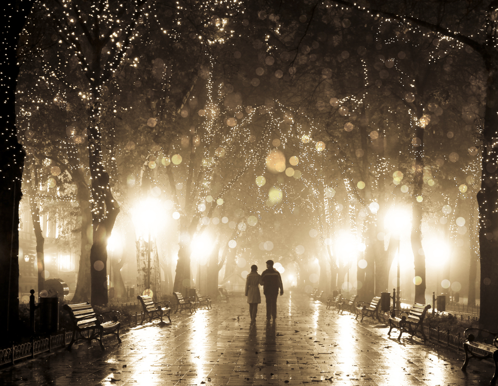 A couple walking between trees at night
