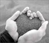 2 hands creating a heart shape with sand