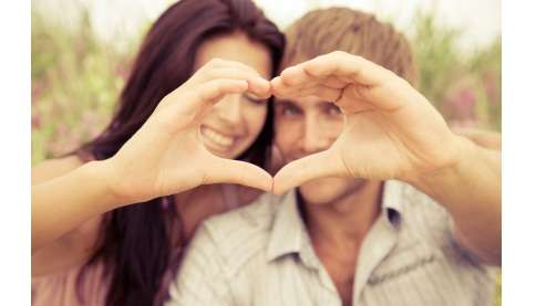 Couple making a heart shape with hands