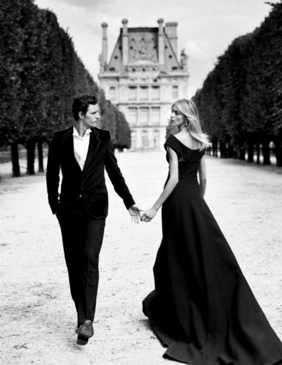 A couple dressed in evening wear holding hands