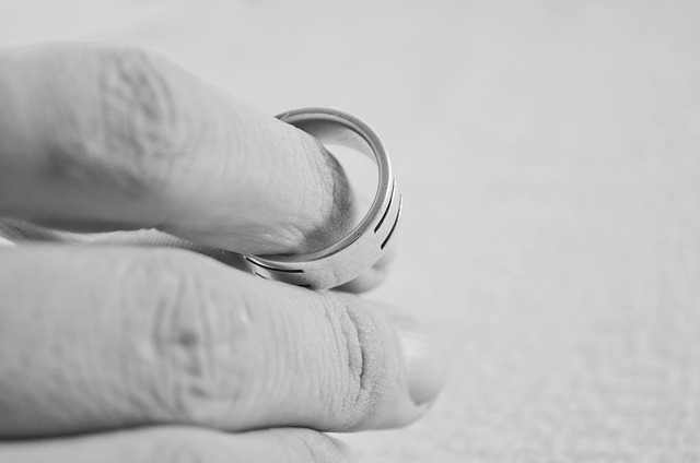 A man holding his wedding ring between his fingers